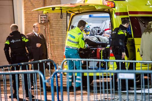 Bert Jonker, schaatssponsor van de ploeg Clafis wordt de ambulance in geholpen. Jonker raakte gewond bij een schietincident bij ijsstadion Thialf