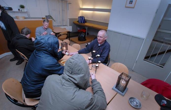 Voorzitter van Jan de Vries van Stoelenproject De Duif (rechts) kijkt toe hoe de daklozen in de opvang hun soep genieten.