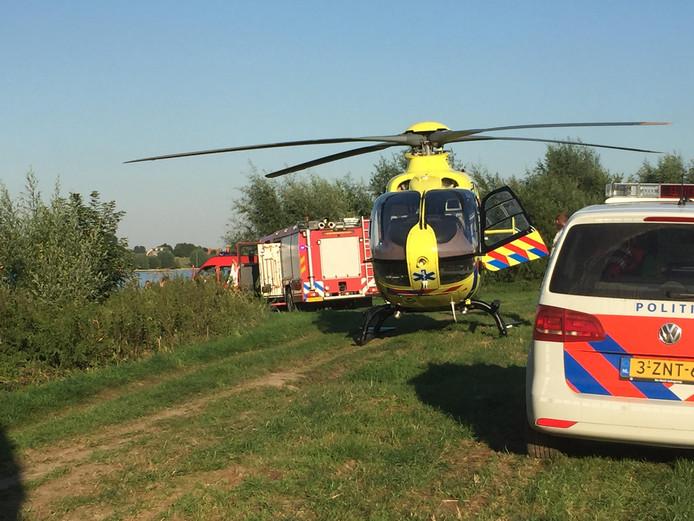 Politie, brandweer en traumahelikopter op de oever van de Waal om te zoeken.