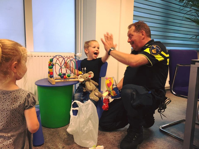 Stan geeft een high five aan een politieagent.