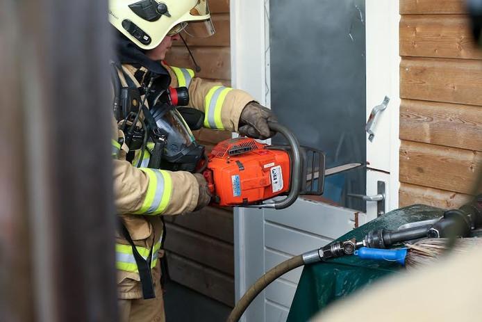 Een brandweerman zaagt een gat in de deur om de rokende pan te kunnen blussen.