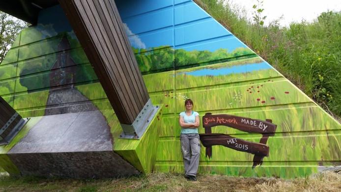Judith Woordes-Scheepers bij de door haar beschilderde fietsbrug over de N18. Foto PR