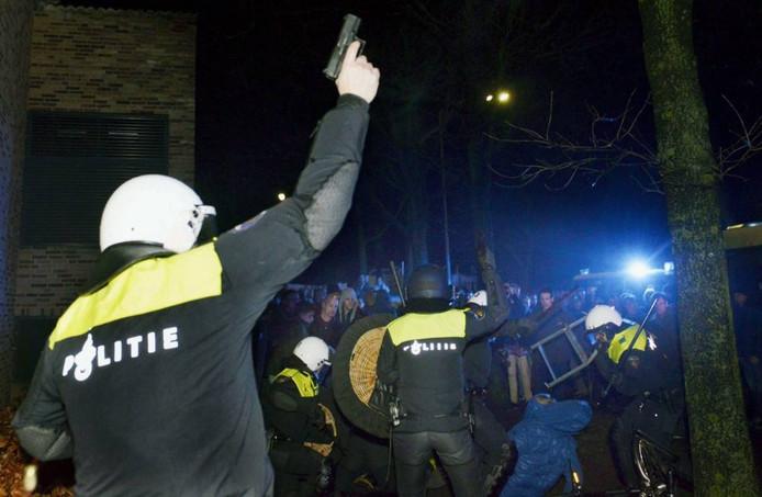 Een agent lost een waarschwingsschot tijdens de rellen in Geldermalsen. Foto: