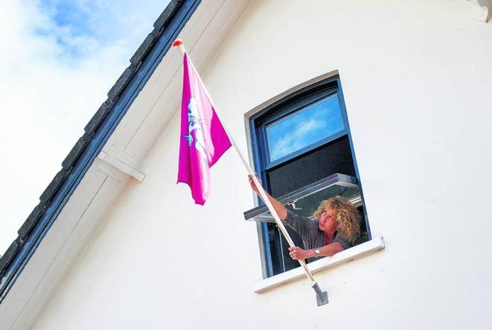 Etske Thie hangt de Airbornevlag uit aan de Weverstraat in Oosterbeek. foto rolf hensel