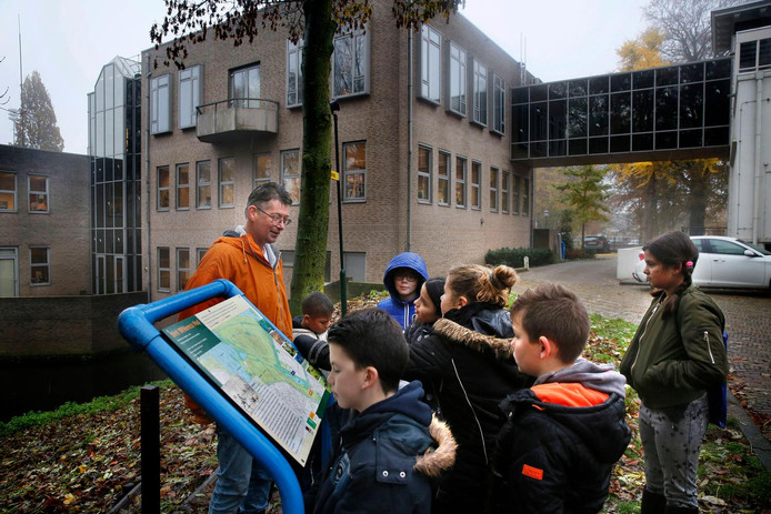 Scholieren bij de zuil met informatie over het Dirk Willemszpad krijgen uitleg van Gijs de Man.