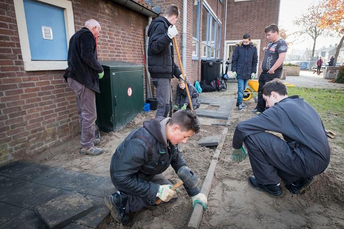 Leerlingen van het Bemmelse Pro College leggen een tegelpad aan in de Cuperstraat.