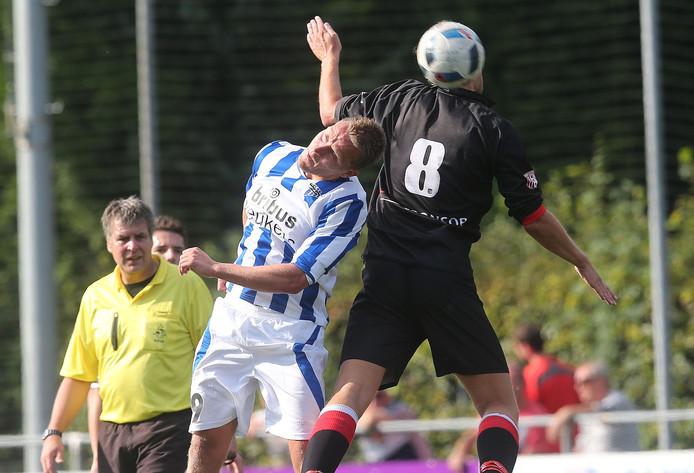 DZSV-speler Daan Harbers (midden) kopt de bal weg voor zijn opponent van IJVV.