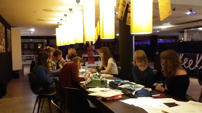 Bezoekers van het festival werken aan een literair tijdschrift.