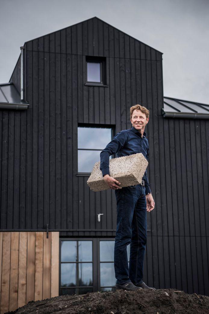Van buiten lijkt Gerrit Hiemstra's huis vooral van hout, maar de muren zijn van kalkhennep. De weerpresentator van de NOS toont trots een blok, dat veel minder milieu-impact heeft.