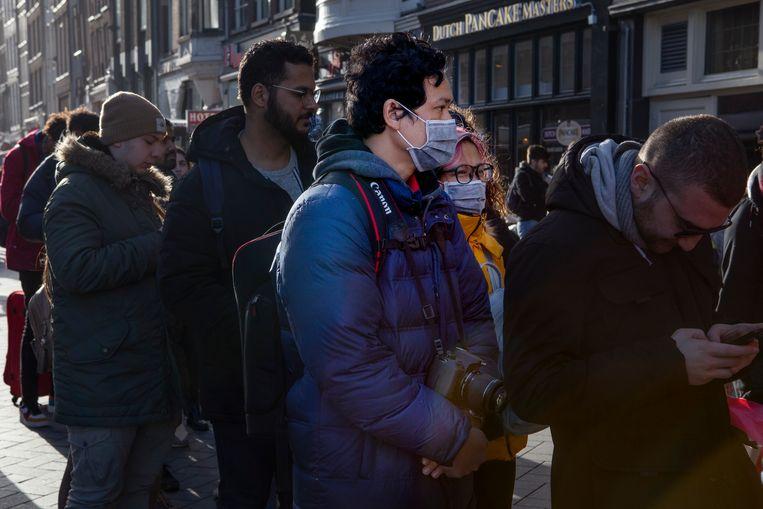 Toeristen in de binnenstad van Amsterdam nemen voorzorgsmaatregelen tegen besmetting van het coronavirus. Beeld Pauline Niks
