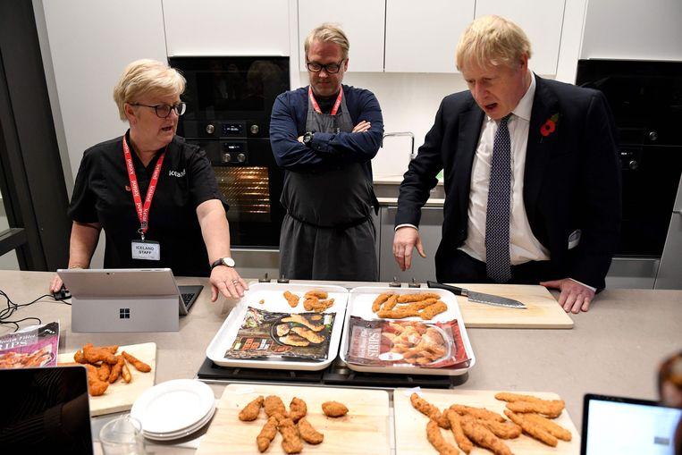 Boris Johnson leert bij over de kwaliteitscontrole van gefrituurde kip in het hoofdkwartier van Iceland Foods in Deeside, Wales.