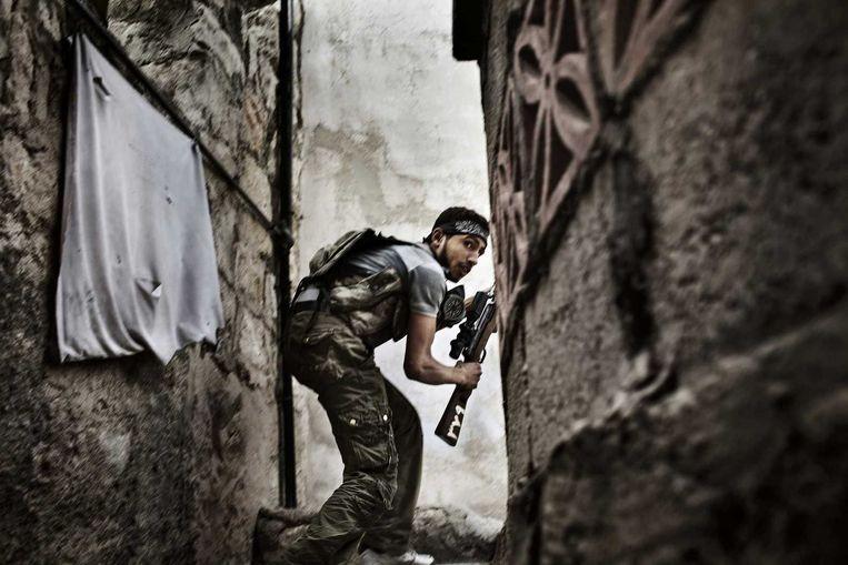 Een strijder van het Vrije Syrische Leger neemt positie in tijdens gevechten met het regeringsleger in de wijk Sulemain Halabi. Beeld AFP