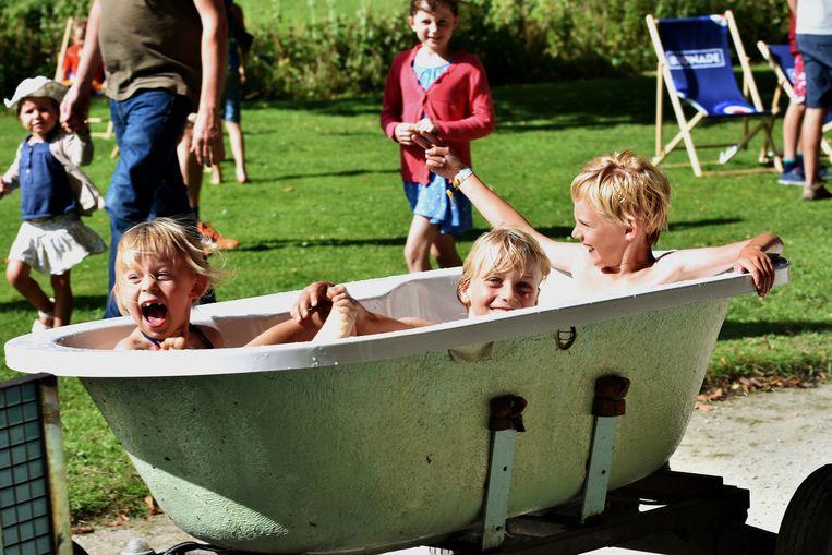 Kinderen amuseren zich te pletter in een rijdend bad.
