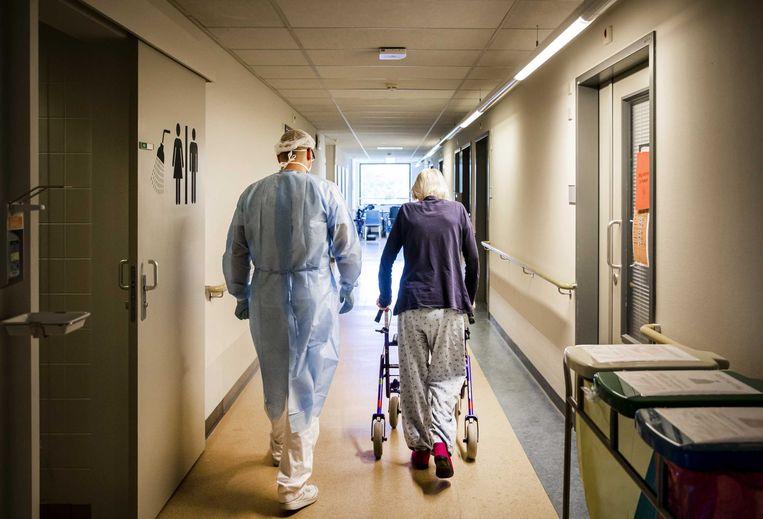 Een fysiotherapeut doet oefeningen met een coronapatiënt in het Amphia Ziekenhuis in Breda. Beeld ANP