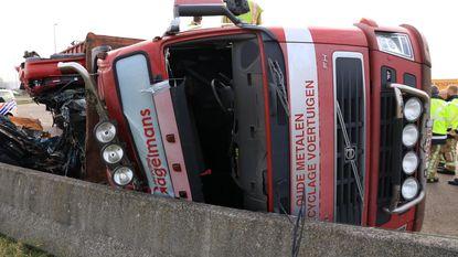 Vrachtwagen met autowrakken kantelt op rotonde