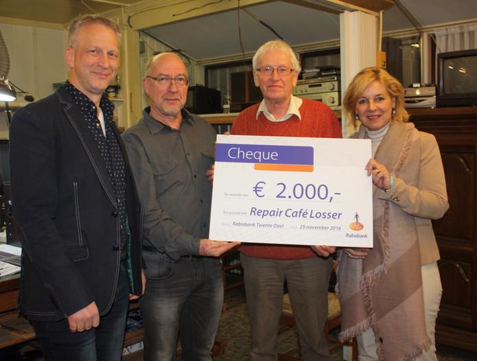 L. Kühlkamp (links) en R. Hanterink (rechts) overhandigen namens het Coöperatiefonds van de Rabobank een cheque ter waarde van 2.000 euro aan T. Vaneker (2e van links) en D. Olthuis, beiden als vrijwilliger actief voor het Repaircafé in Losser.