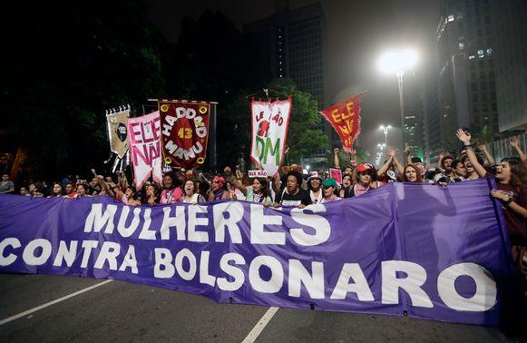 Vrouwen demonstreren tegen Bolsonaro. 'Vrouwen tegen Bolsonaro' staat in koeienletters op het spandoek geschreven.