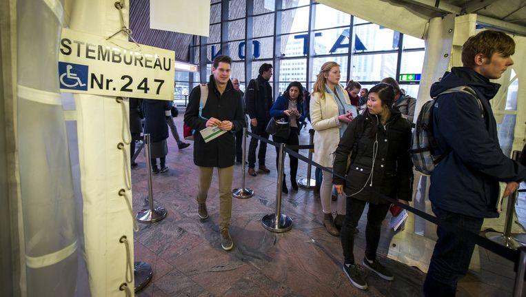 Reizigers brengen hun stem uit voor de Provinciale Statenverkiezingen op station Rotterdam Centraal. Beeld anp