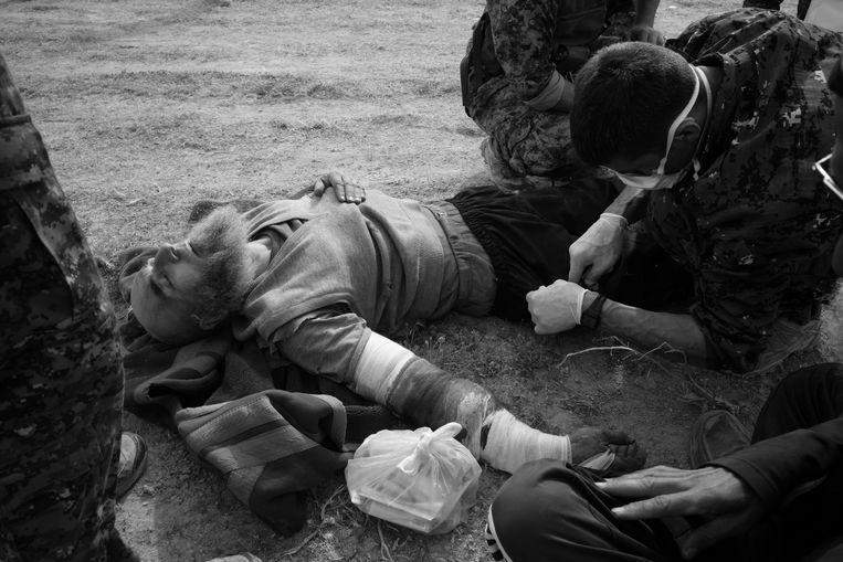 Een zwaar gewonde IS strijder wordt ter plaatse behandeld, zijn overlevingskans is vrij klein, het transport naar de gevangenis kan vele uren tot een dag duren. Beeld Eddy van Wessel