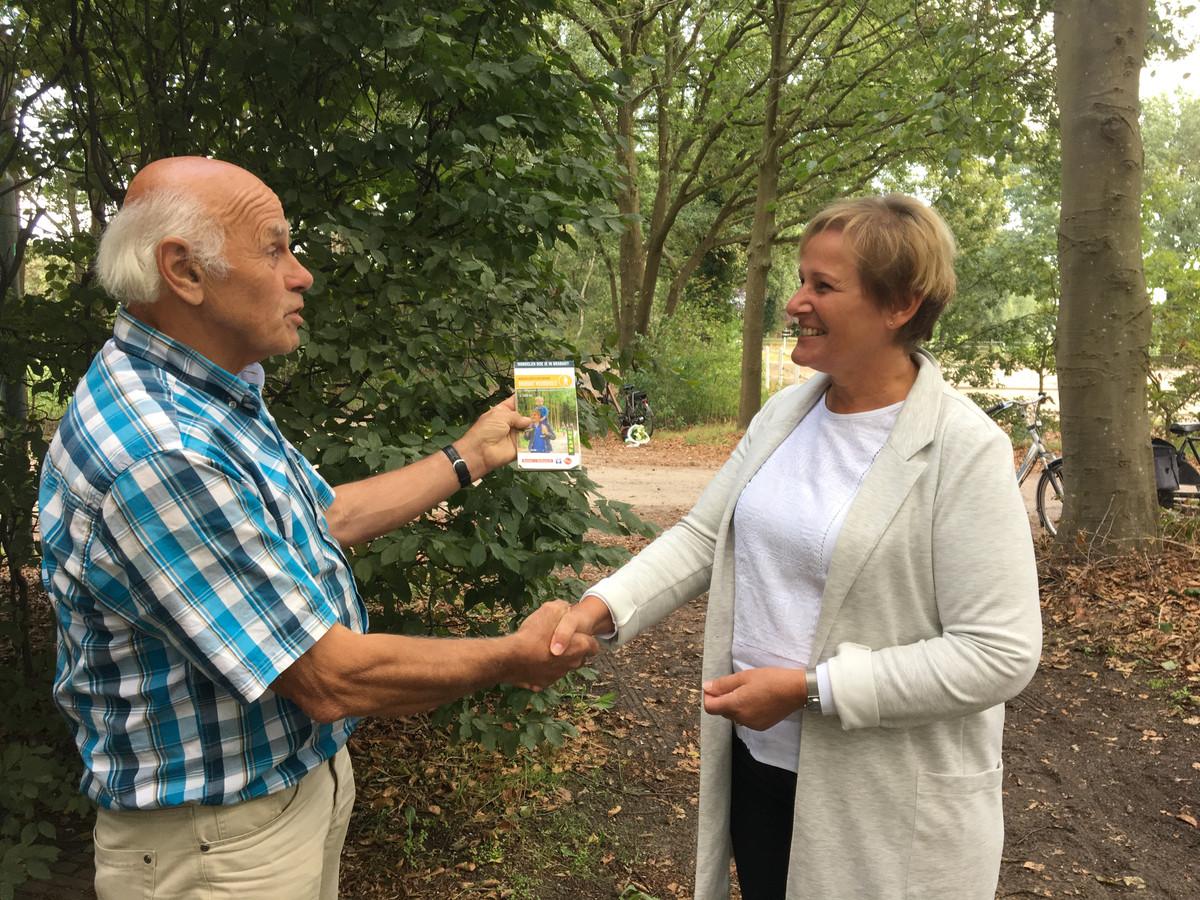 Wethouder Coby van der Pas ontvangt de nieuwe wandelroutekaart van Meierijstad uit handen van vrijwilliger Martien Verbakel.