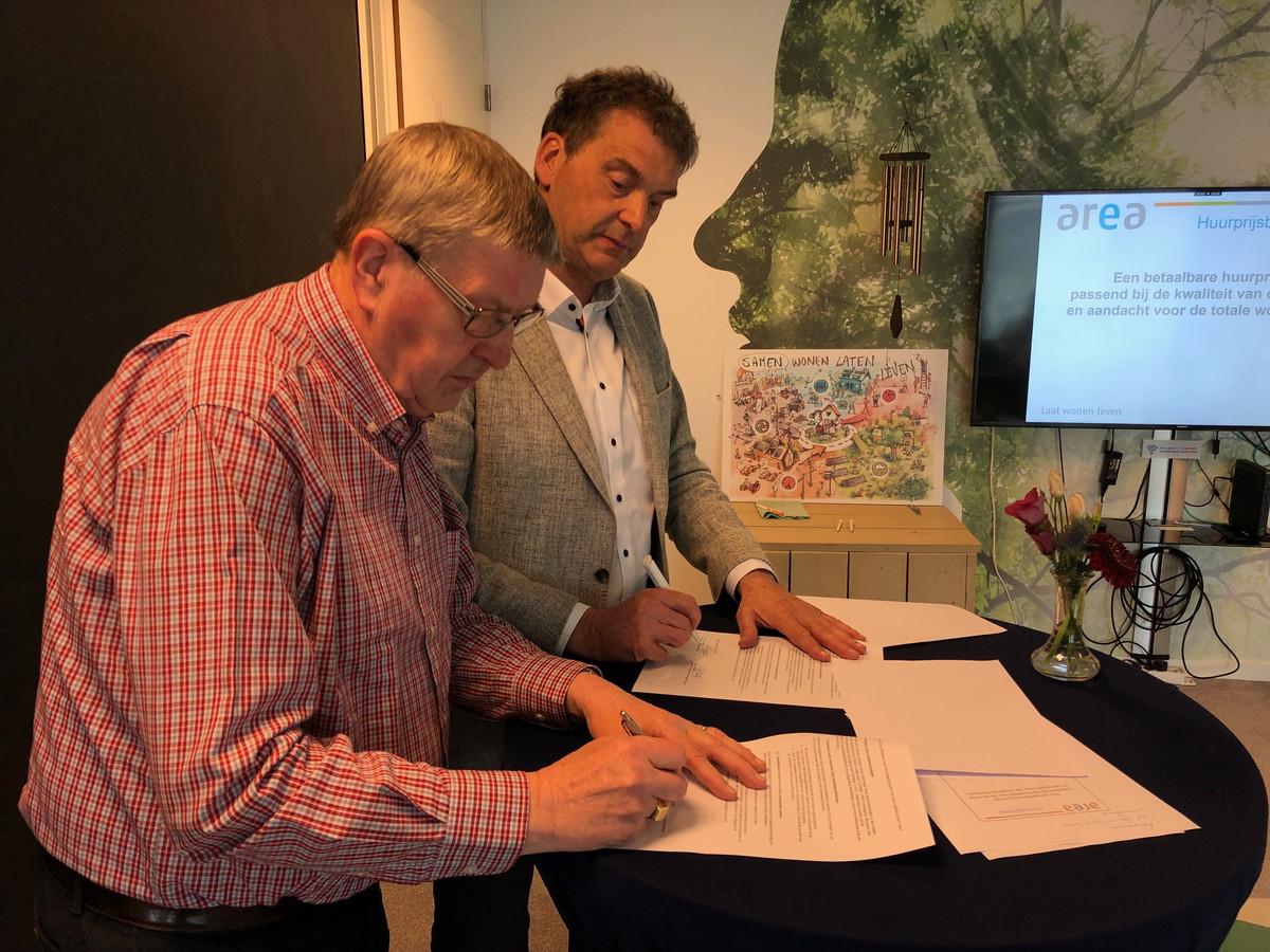 Voorzitter Riny van Dijk van de bewonersraad van Area (links) tekent samen met directeur-bestuurder Jan van Vucht van Area het lokaal huurakkoord dat voor de komende drie jaar uitgaat van een gematigde huurverhoging voor de meeste van de 8000 huurders in Uden en Veghel.