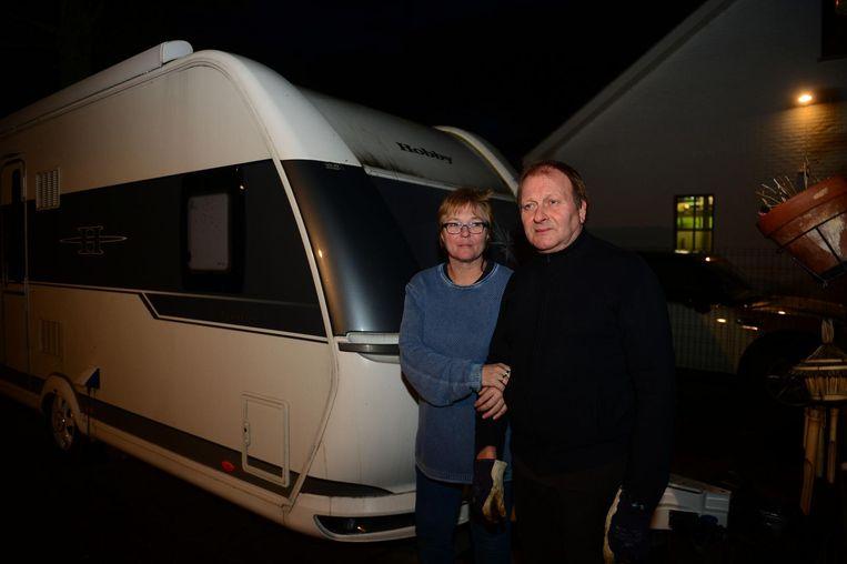 Bewoners Annette Belien en Michael Wellens naast hun caravan van 25.000 euro, die de boom op het nippertje gemist heeft.