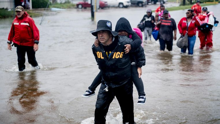Een agent draagt een kind op de rug in Houston. Beeld afp