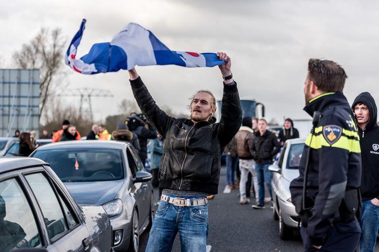 Een Friese demonstrant zwaait met een Friese vlag. Beeld null