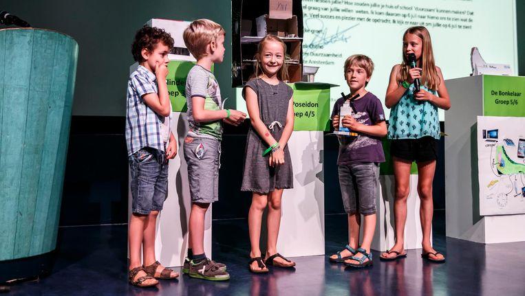 Leerlingen van Poseidon tijdens het pitchen van hun winnende idee: een school met waterzuiveringsinstallatie, smart prullenbak, zonnepanelen en een kachel die brandt door de zonnehitte Beeld Carly Wollaert