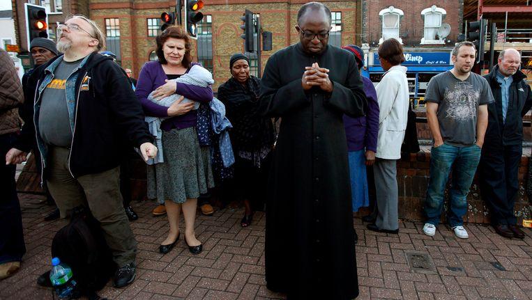 Kerkgangers bidden op straat voor een kerk in Tottenham. Beeld EPA