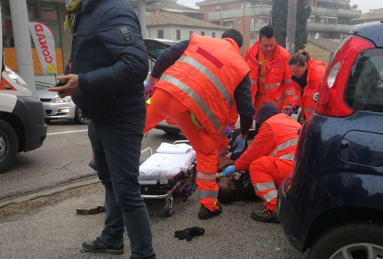 Medisch personeel op 3 februari aan de slag bij een slachtoffer van Luca Traini in Macerata.   Beeld REUTERS