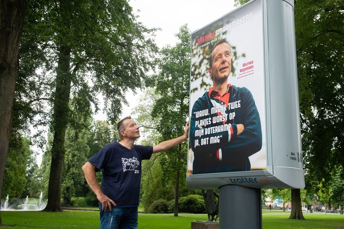 Breda - Voorzitter van de Bredase Zomerkampen, Wilfred Huijsmans, naast zijn portret voor Bredase Smaakmakers op een expositie in stadspark Valkenberg in Breda.