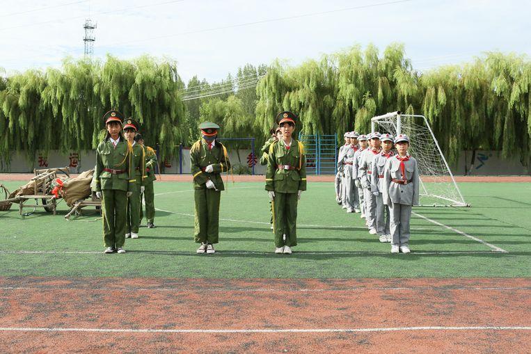 Basisschoolleerlingen van de Rode Leger School in Yi'nan (Shandong) maken zich klaar voor de wekelijkse vlaggenceremonie.  Beeld Elke Scholiers
