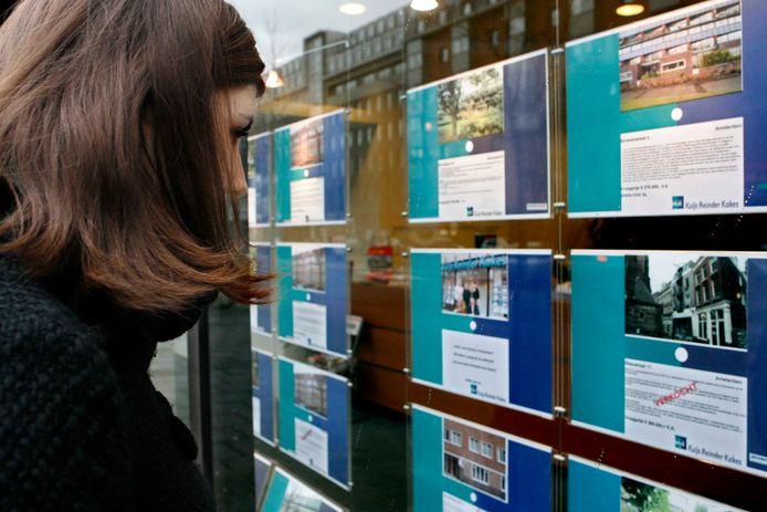 Een voorbijganger bekijkt het woningaanbod in een etalage van een NVM makelaar.