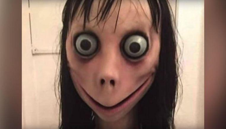 De figuur uit de Momo Challange lijkt met haar grote ogen, lange haar en grimmige lach rechtstreeks uit een nachtmerrie ontsnapt.