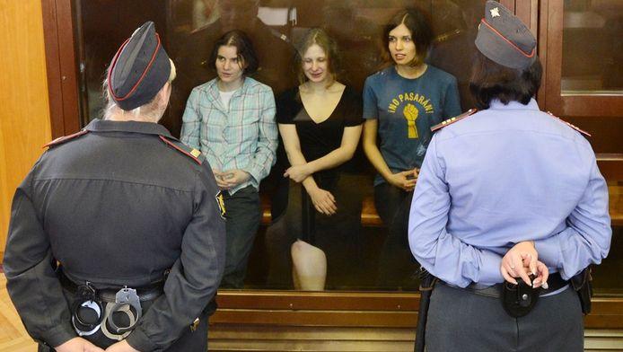 De drie Pussy Riot-leden wachten in een glazen kooi op de uitspraak.