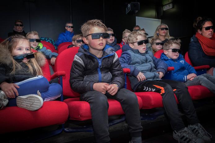 Kinderen en enkele ouders in de nieuwe bioscoopzaal van pretpark Tivoli in Berg en Dal.