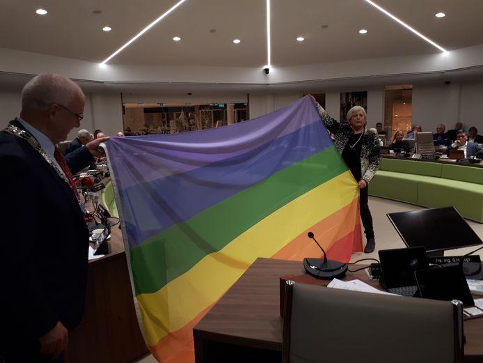 Marijke Gommans (D66)  en burgemeester Jan Heijkoop ontvouwen de regenboogvlag. Rechts van Gommans de lege stoelen van Leo Platschorre en Peter Boudewijn.