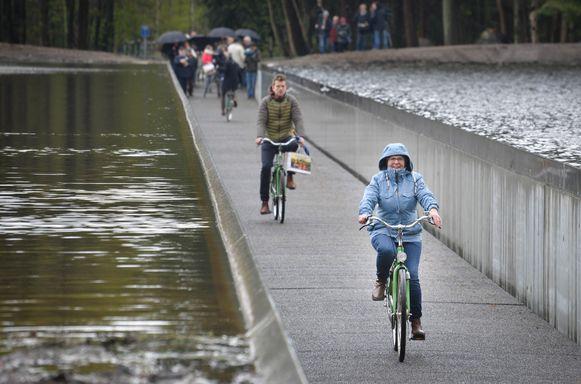 De mensen fietsen als het ware door de vijver heen. Het water stroomt ter hoogte van hun gezicht.