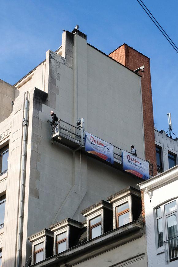 Medewerkers van de stad Brussel overschilderen de tekening (foto links).