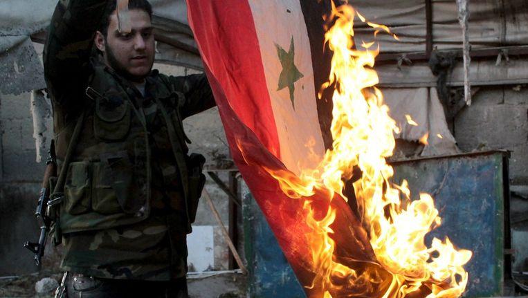 Een Syrische rebel verbrandt een overheidsvlag. Beeld afp