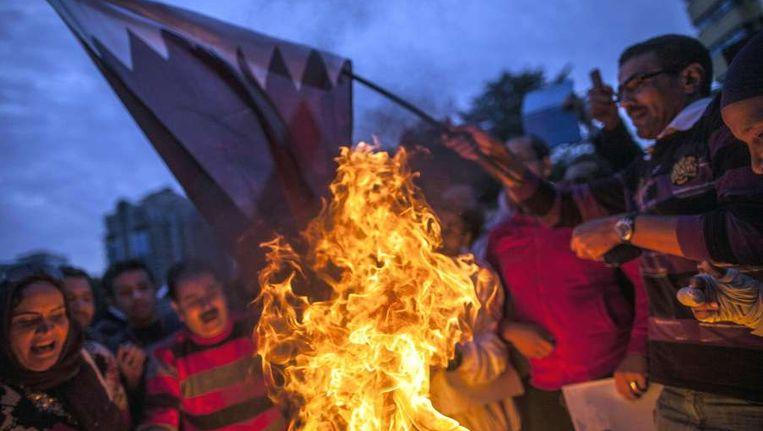 Aanhangers van de militaire leider van Egypte verbranden een Qatarese vlag. Beeld afp