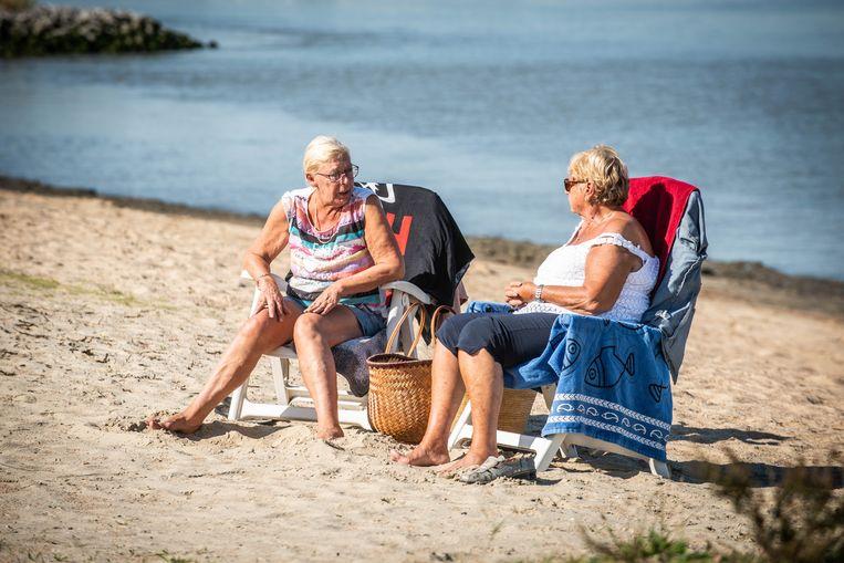 Deze twee dames op het Antwerpse strand van Sint-Anneke weten het wel: voetjes in het zand, schouders bloot, benen laten blinken in de zon en hup, genieten maar.