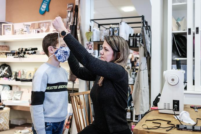Susanne Janssen past een mondkapje bij haar zoon Lucas. Foto : Jan Ruland van den Brink