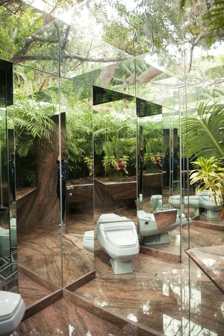 Junglehuis Het huis is een verlengstuk van de extravagante jungle rondom de woning. Of is het andersom? Het gastentoilet is daar een goed voorbeeld van: door de spiegels en ramen ben je er haast midden in de natuur. Het plafond kan ook nog eens open. Beeld Els Zweerink