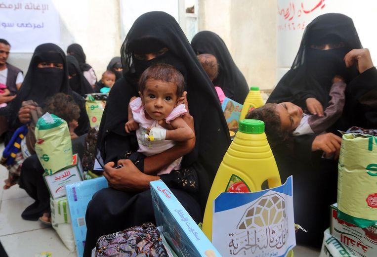 Jemenitische vrouwen en kinderen wachten tijdens een voedseldistributie in de havenstad Hodeida.  Beeld AFP