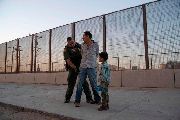 Een Amerikaanse agent fouilleert een Centraal-Amerikaanse migrant in El Paso, Texas, terwijl het zoontje van de migrant toekijkt.
