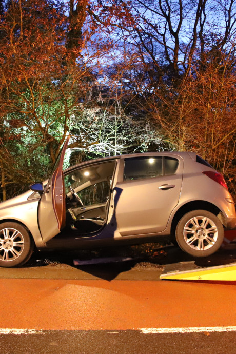 Auto rijdt omheining en verkeerspaaltje uit de grond in Asch