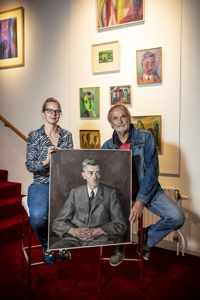 Initiatiefnemers Evelien Snijders en Henk Lassche met een portret van Haanstra senior, geschilderd door zoon Johan.