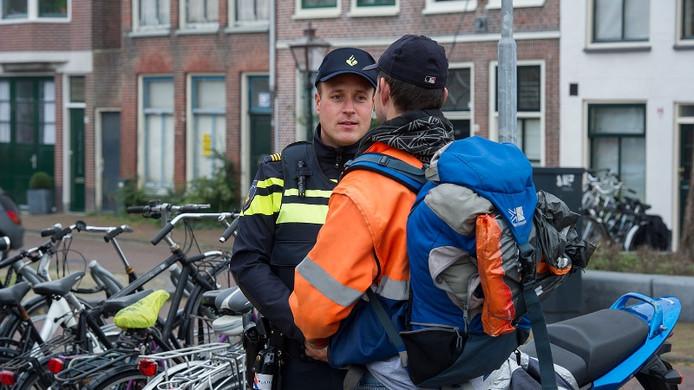 Man met een rugzak praat met een politieagent. Foto ter illustratie.